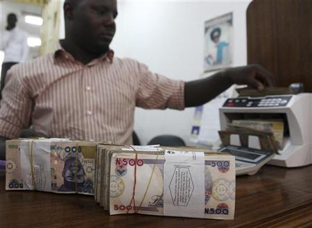 A money dealer counts the Nigerian naira on a machine in his office in the commercial capital of Lagos
