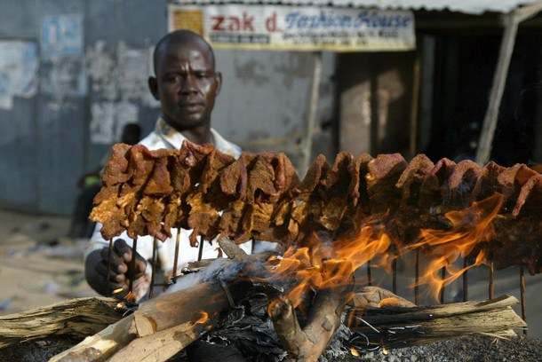 A man arranges sticks of meat on a mud p